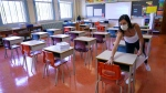 Grade one teacher Heidi Dimou arranges the desks in line with physical distancing policy in her class in preparation for the new school year at the Willingdon Elementary School in Montreal, on Wednesday, August 26, 2020. THE CANADIAN PRESS/Paul Chiasson