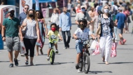 People wear face masks as they walk along a pedestrian zone on Saint-Laurent Boulevard in Montreal, Saturday, August 15, 2020, as the COVID-19 pandemic continues in Canada and around the world. THE CANADIAN PRESS/Graham Hughes