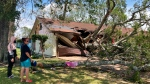 Maria Ramirez and her son 17-year old son Jose Avila stand in front of their home in Orange, Texas, Thursday, Aug. 27, 2020, and survey damage after a portion of the large tree on their front lawn was blown down onto their house by Hurricane Laura's winds. Ramirez, 57, said the tree crashed through her garage and also damaged her living room and kitchen. Ramirez said she her family had evacuated to Houston before the storm came ashore and were not at home when the tree fell. (AP Photo/Juan Lozano)