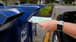 In this Tuesday, Aug. 18, 2020, file photo, a person drops applications for mail-in-ballots into a mail box in Omaha, Neb. (AP Photo/Nati Harnik, File)