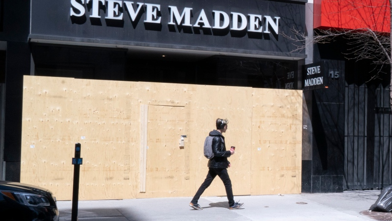 A pedestrian walks past a boarded store on Montreal's Ste-Catherine street, on Tuesday, April 28, 2020. THE CANADIAN PRESS/Paul Chiasson