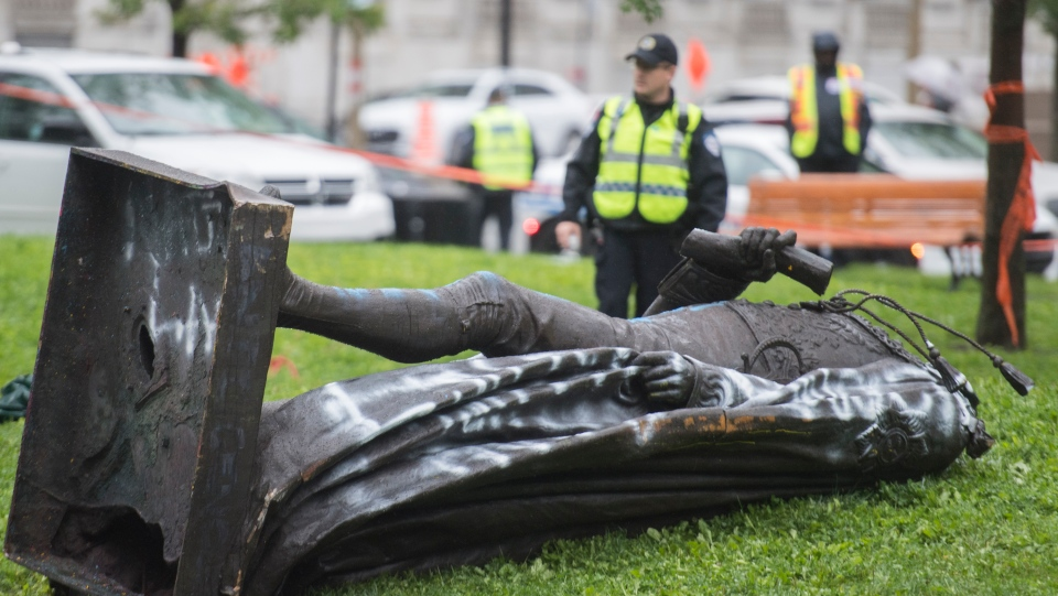 Police officers are shown at the scene next to the statue of Sir John A. Macdonald after it was torn down following a demonstration in Montreal, Saturday, Aug. 29, 2020, where people protested to defund the police with a goal to end all systemic racism within all sectors of the Canadian government. (THE CANADIAN PRESS/Graham Hughes)