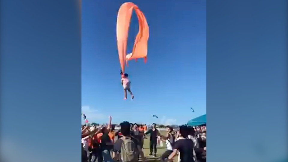 In this image made from video, a three-year-old girl is lifted into the air by a large kite during a kite festival in Hsinchu, northern Taiwan, Sunday, Aug. 30, 2020. The wind slowed down and the girl was safely recovered by adults on the ground. (Credit: Dainese Hsu)