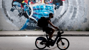 A man wears a face mask as he cycles by a mural defaced by graffiti objecting to mask usage as a measure to protect against the spread of COVID-19, in Montreal, Sunday, Aug 30, 2020, as the pandemic continues in Canada and around the world. THE CANADIAN PRESS/Graham Hughes