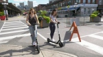 Two women ride e-scooters in Ottawa's ByWard Market, Aug. 31, 2020. (Dave Charbonneau / CTV News Ottawa)