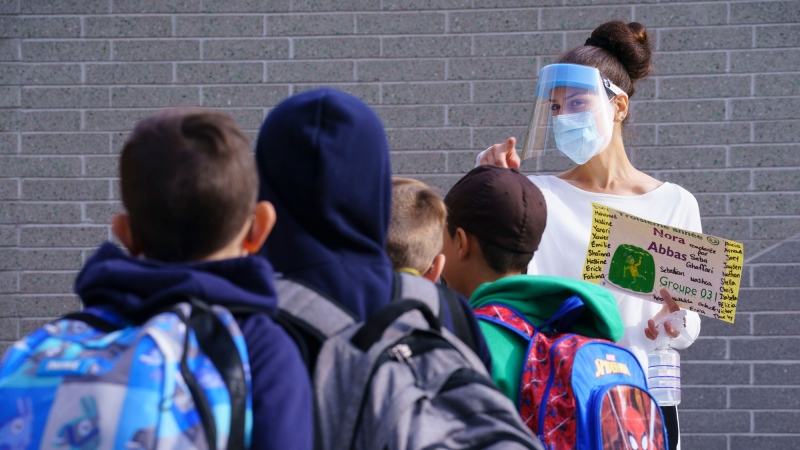 A teacher wearing protective equipment greets her students in the school yard at the Philippe-Labarre Elementary School in Montreal, on Thursday, August 27, 2020. THE CANADIAN PRESS/Paul Chiasson