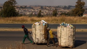 Men pull trolleys filled with cardboard and plastic bottles for recycling at Phumlamqashi informal settlement in Vlakfontein near Johannesburg, South Africa, on June 3, 2020. (Themba Hadebe / AP)
