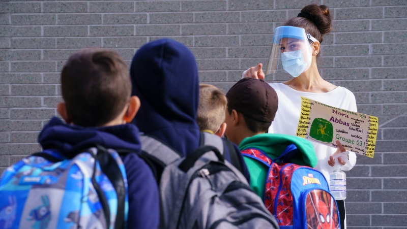 A teacher wearing protective equipment greets her students in the school yard at the Philippe-Labarre Elementary School in Montreal, on Thursday, August 27, 2020. Thousands of Quebec students return to class in the shadow of the COVID-19 pandemic. THE CANADIAN PRESS/Paul Chiasson