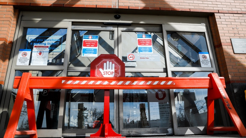 An entrance is blocked to the Peter Lougheed Centre hospital so staff can screen essential visitors who are the only visitors permitted in Alberta hospitals as part of COVID-19 precautions in Calgary, Alta., Thursday, April 9, 2020. THE CANADIAN PRESS/Jeff McIntosh​
