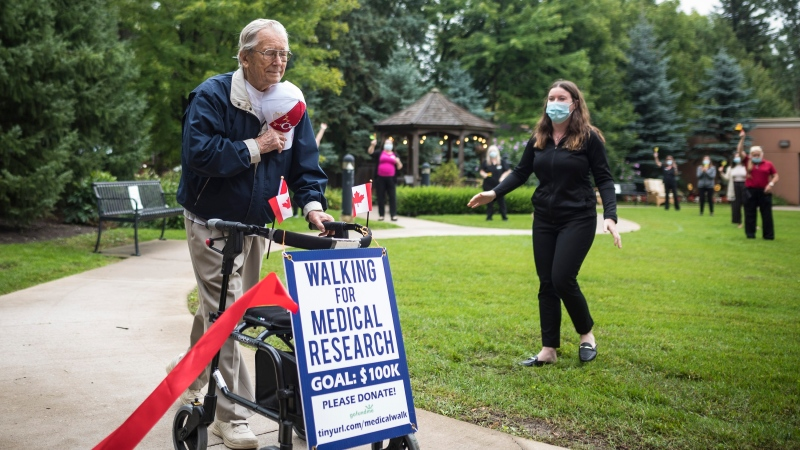 George Markow, a 99-year-old Second World War Veteran, crosses the finish line after completing his 100 km walking milestone, in a special fundraising effort to raise $100,000 for COVID-19 medical research, at the Roxborough Retirement Residence in Newmarket, Ont., on Wednesday, September 2, 2020. (THE CANADIAN PRESS/ Tijana Martin)
