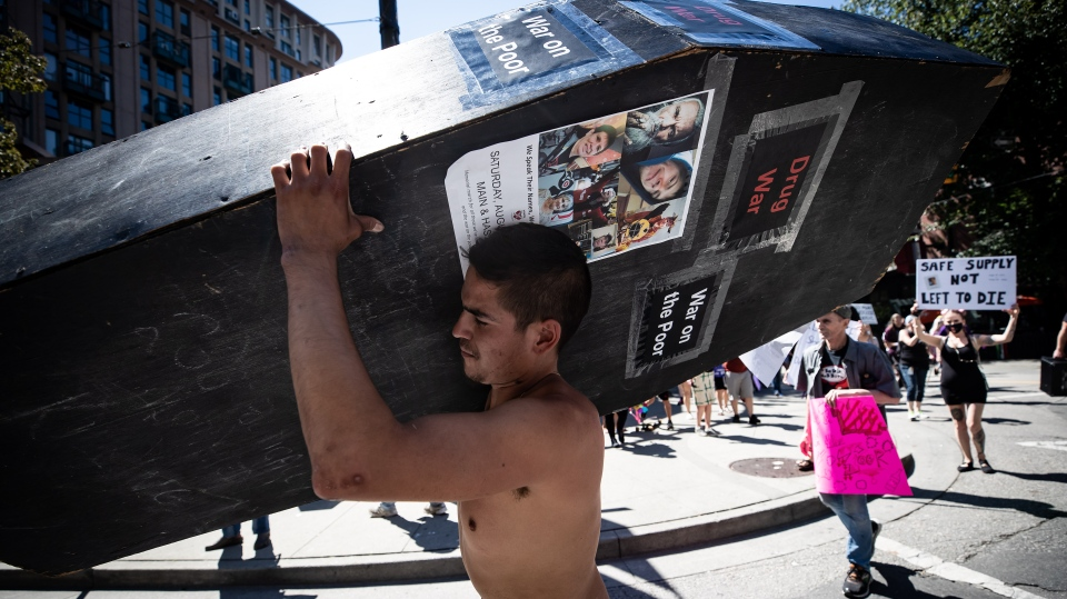 A man carries a coffin during a memorial march to remember victims of overdose deaths in Vancouver on Saturday, August 15, 2020. (Photos from Darryl Dyck / The Canadian Press)