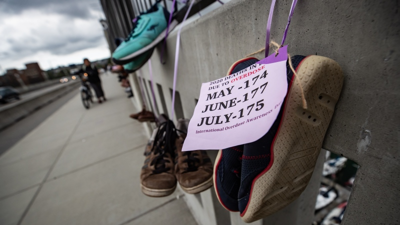 Pairs of shoes line Vancouver's Burrard Street Bridge in memory of those who have died of overdose. (Photo from Darryl Dyck / The Canadian Press, captured on Monday, Aug. 31, 2020 – International Overdose Awareness Day)