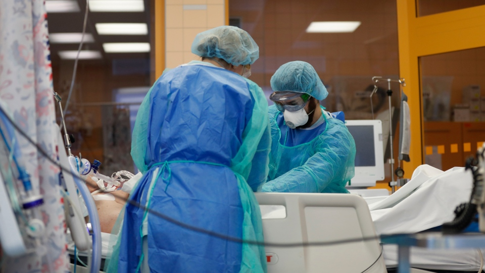 Healthcare workers attend to a COVID-19 patient in an intensive care unit (ICU) at the General University Hospital in Prague, Czech Republic, Tuesday, April 7, 2020. (AP Photo/Petr David Josek)