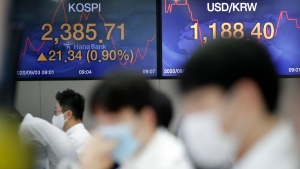 Currency traders watch computer monitors near the screens showing the Korea Composite Stock Price Index (KOSPI), left, and the foreign exchange rate between U.S. dollar and South Korean won at the foreign exchange dealing room in Seoul, South Korea, Thursday, Sept. 3, 2020. (AP Photo/Lee Jin-man)