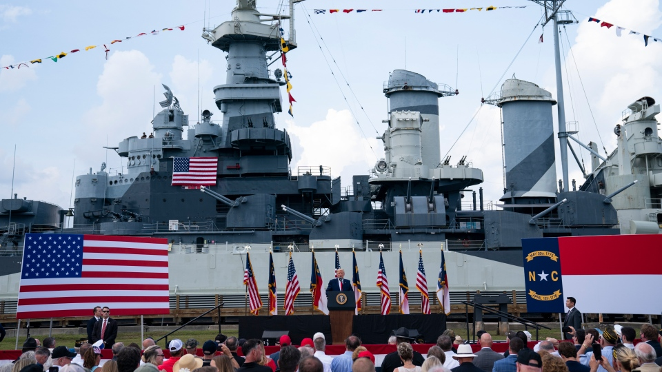 With the USS Battleship North Carolina in the background, U.S. President Donald Trump speaks during an event to designate Wilmington as the first American World War II Heritage City, Wednesday, Sept. 2, 2020, in Wilmington, N.C. (AP Photo/Evan Vucci)