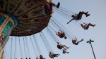 Children swing on a midway ride at the 140th annual Canadian National Exhibition in Toronto on Sunday, August 19, 2018. The Canadian National Exhibition has been cancelled by the COVID-19 pandemic. THE CANADIAN PRESS/Cole Burston