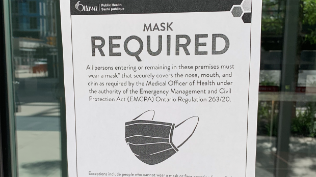 A sign requiring mask be worn in common areas of condo and apartment buildings is posted on a door in Ottawa. (Leah Larocque/CTV News Ottawa)