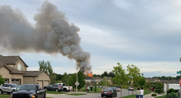 Flames and smoke are seen in the neighbouring subdivision where a vintage barn off Fanshawe Park Road caught fire in London, Ont. on Wednesday, Sept. 2, 2020. (Viewer Photo)