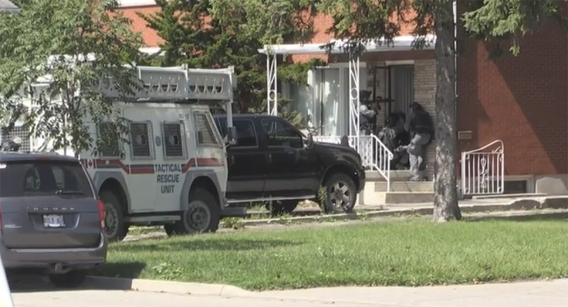 Armed officers stand at the door of a home on Regent Street in London, Ont. on Thursday, Sept. 3, 2020. (Daryl Newcombe / CTV News)