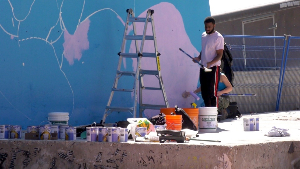 Calgary artist Jae Sterling works on a mural in Chinatown, titled The Guide & Protector. Some in the Chinese community say there was a lack of consultation around the project.