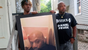 """Joe Prude, brother of Daniel Prude, right, and his son Armin, stand with a picture of Daniel Prude in Rochester, N.Y., on Thursday, Sept. 3, 2020. Prude suffocated after police in Rochester put a """"spit hood"""" over his head while being taken into custody. He died March 30, after he was taken off life support, seven days after the encounter with police. (AP / Ted Shaffrey)"""