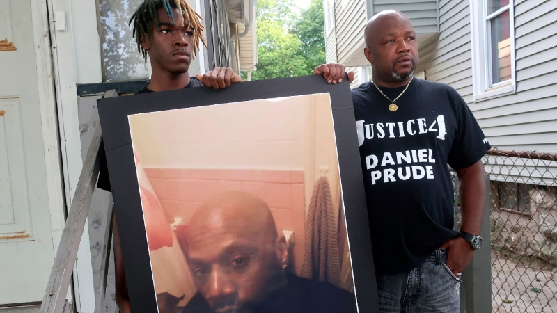 "Joe Prude, brother of Daniel Prude, right, and his son Armin, stand with a picture of Daniel Prude in Rochester, N.Y., on Thursday, Sept. 3, 2020. Prude suffocated after police in Rochester put a ""spit hood"" over his head while being taken into custody. He died March 30, after he was taken off life support, seven days after the encounter with police. (AP / Ted Shaffrey)"