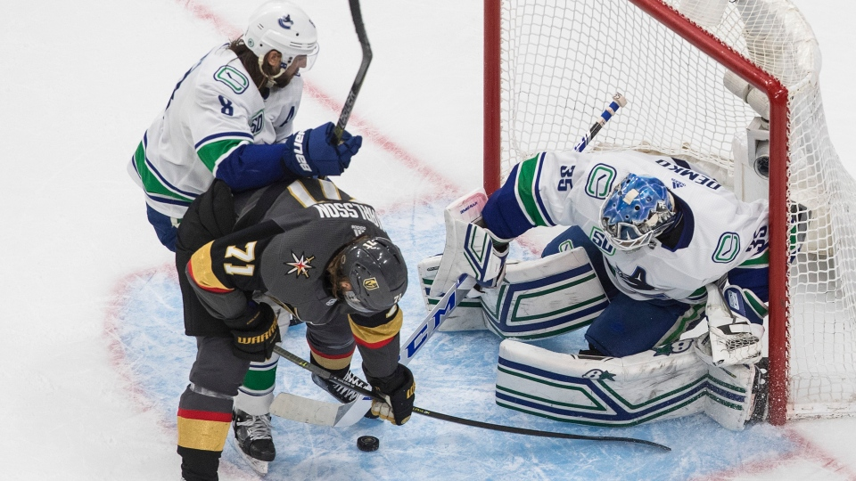 Vancouver Canucks goalie Thatcher Demko (35) makes the save on Vegas Golden Knights' William Karlsson (71) as Christopher Tanev (8) defends during third period NHL Western Conference Stanley Cup playoff action in Edmonton on Friday, September 4, 2020. THE CANADIAN PRESS/Jason Franson