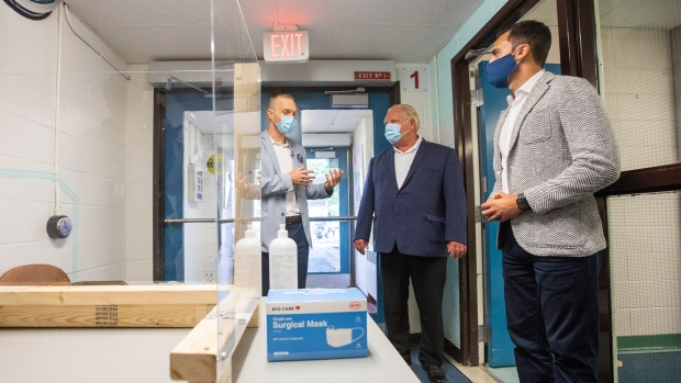 Principal Dan Fisher, left, of Kensington Community School gives a tour to Ontario Premier Doug Ford, centre, and Education Minister Stephen Lecce to see the safety measures implemented as students return to school amidst the COVID-19 pandemic on Tuesday, September 1, 2020. THE CANADIAN PRESS/Carlos Osorio