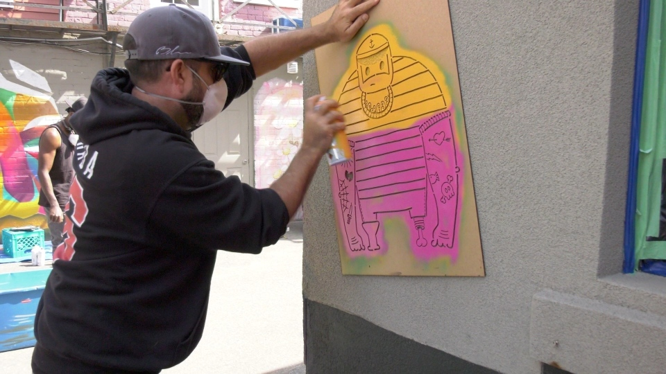 Street artist TRP613 putting up his famous sailor on the wall of the Arlington Five coffee shop in Ottawa. (Dave Charbonneau / CTV News Ottawa)