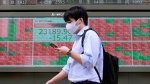 A man walks by an electronic stock board of a securities firm in Tokyo, Monday, Sept. 7, 2020. (AP Photo/Koji Sasahara)