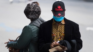 A man wears a face mask as he sits on a street in Montreal, Saturday, Sept. 5, 2020, as the COVID-19 pandemic continues in Canada and around the world. THE CANADIAN PRESS/Graham Hughes