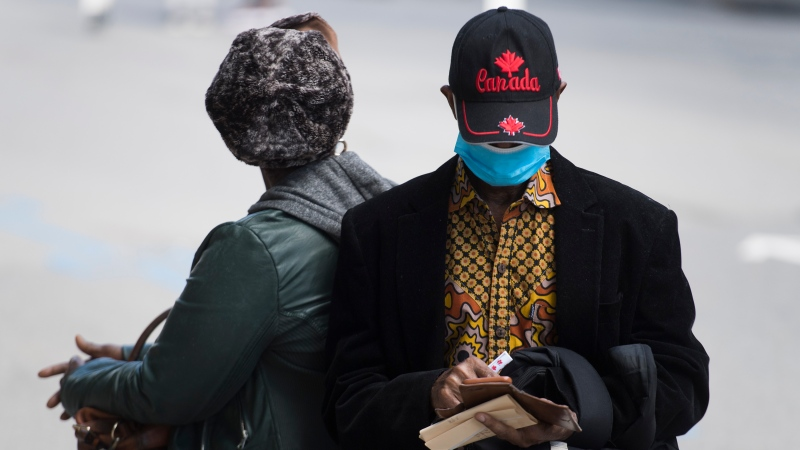 A man wears a face mask while sitting in Montreal. The COVID-19 pandemic continues in Canada and around the world. THE CANADIAN PRESS/Graham Hughes
