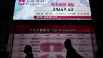 People walk past a bank's electronic board showing the Hong Kong share index in Hong Kong, Tuesday, Sept. 8, 2020. (AP Photo/Vincent Yu)