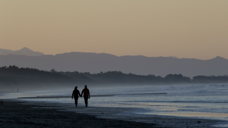 A couple walk along New Brighton Beach at sunset in Christchurch, New Zealand, Tuesday, June 9, 2020. (AP Photo/Mark Baker)