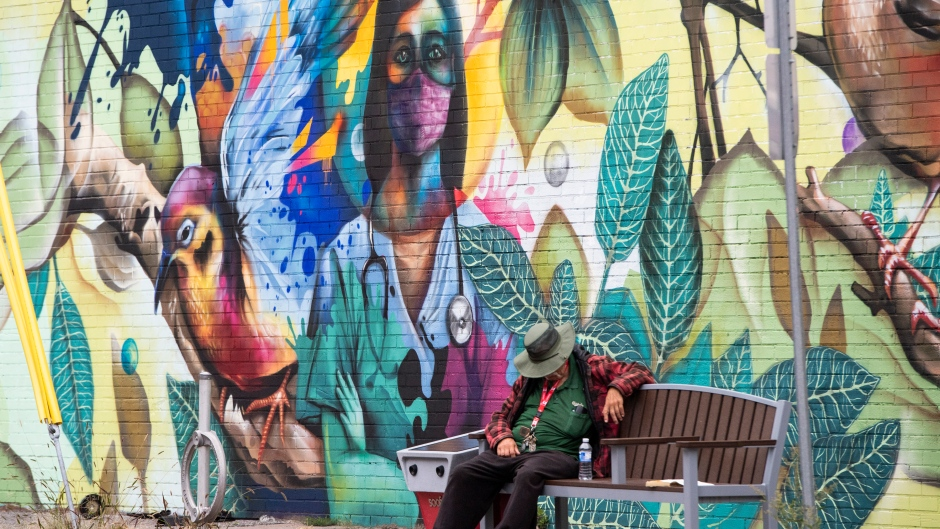 A person rests on a bench by a mural by artist Dom Laporte showing a health care worker, in Ottawa, on the Labour Day Long Weekend, Monday, Sept. 7, 2020, in the midst of the COVID-19 pandemic. (Justin Tang/THE CANADIAN PRESS)