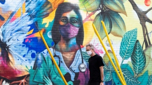 A person walks past a mural by artist Dom Laporte showing a health care worker, in Ottawa, on the Labour Day Long Weekend, Monday, Sept. 7, 2020, in the midst of the COVID-19 pandemic. (Justin Tang/THE CANADIAN PRESS)