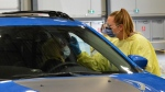 A staff member at the Regina drive-through testing station swabs a woman for COVID-19. (Jeremy Simes/CTV Regina)