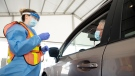 Ottawa Health personnel speak with Roshene Lawson before administering a COVID-19 test at a drive-through test centre in Ottawa, Friday, September 4, 2020. THE CANADIAN PRESS/Adrian Wyld