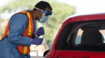 Ottawa Health personnel speak with a driver before administering a COVID-19 test at a drive-through test centre in Ottawa, Friday, September 4, 2020. THE CANADIAN PRESS/Adrian Wyld
