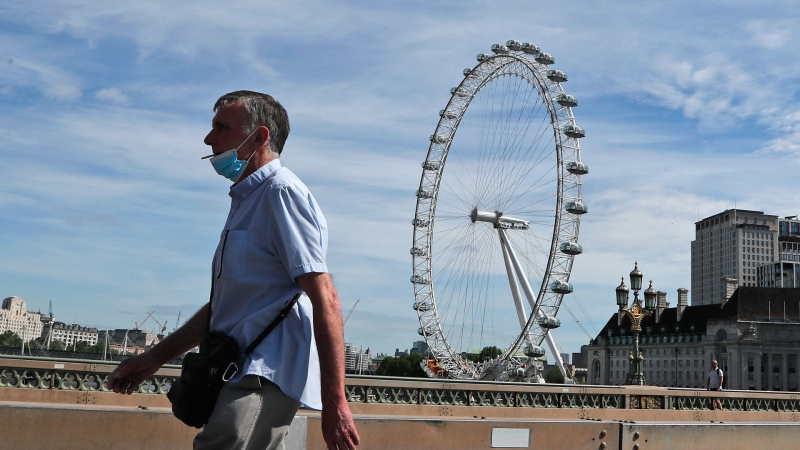 A man wearing a protective mask strolls across a bridge in central London, Tuesday, May 26, 2020, during hot weather following the gradual easing of the COVID-19 lockdown, allowing more outdoor recreation and letting some shops and businesses reopen. (AP / Frank Augstein)