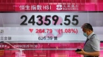 A man walks past a bank's electronic board showing the Hong Kong share index at Hong Kong Stock Exchange Wednesday, Sept. 9, 2020. (AP Photo/Vincent Yu)
