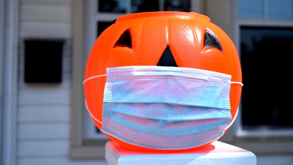 A Halloween treat bucket wearing a face mask. (Shutterstock)