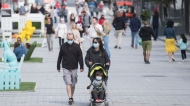 People wear face masks as they walk along a street in Montreal, Saturday, Sept. 5, 2020, as the COVID-19 pandemic continues in Canada and around the world. THE CANADIAN PRESS/Graham Hughes