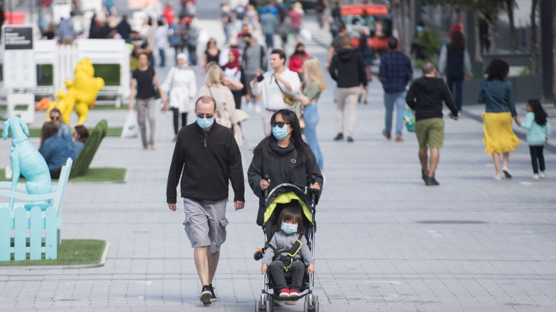 People wear face masks as they walk along a street in Montreal, Saturday, Sept. 5, 2020. THE CANADIAN PRESS/Graham Hughes