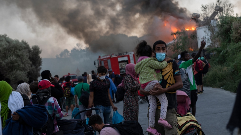Migrants flee from the Moria refugee camp during second a fire, on the northeastern Aegean island of Lesbos, Greece, on Wednesday, Sept. 9, 2020. (AP Photo/Petros Giannakouris)