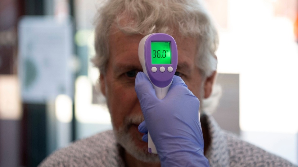 In this Tuesday, June 9, 2020 photo, a patient has his temperature taken with a non-contact infrared thermometer in Grimsby, northeast England. (Daniel Leal-Olivas/Pool Photo via AP)