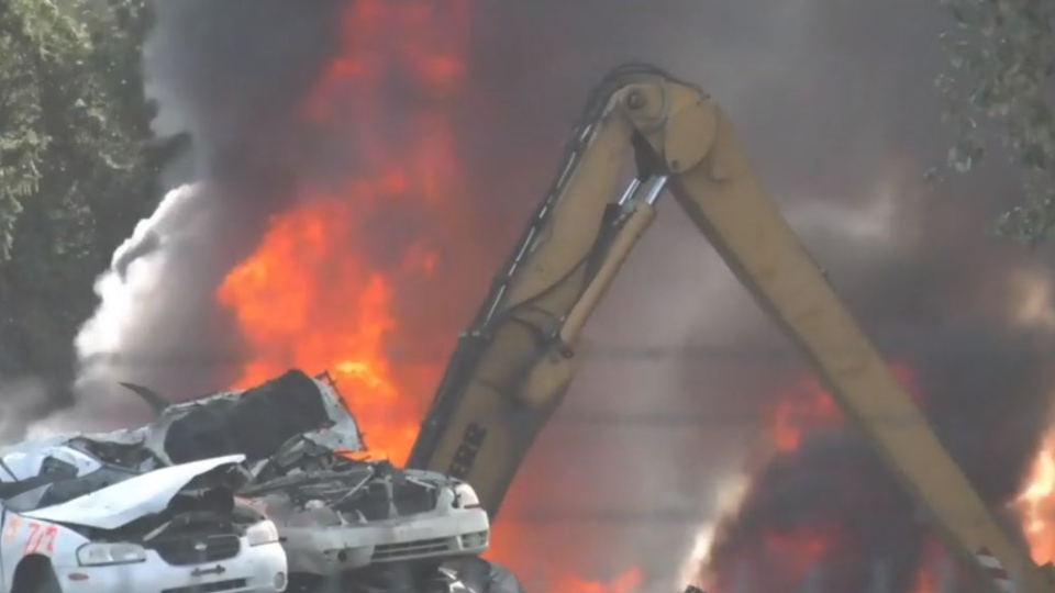 Flames and a massive plume of black smoke are visible at the Schnitzer Steel site near the Nanaimo airport. (CTV News)