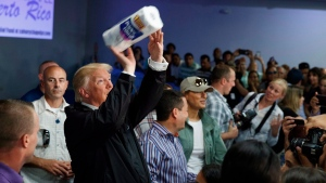 In this Oct. 3, 2017 file photo, U.S. President Donald Trump tosses paper towels into a crowd at Calvary Chapel in Guaynabo, Puerto Rico after Hurricane Maria devastated the region. (AP Photo/Evan Vucci, File)