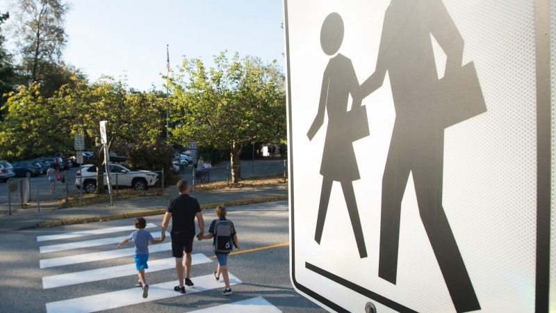 Children walk with their parents to Sherwood Park Elementary in North Vancouver for the first day back-to-school Thursday, September 10, 2020. THE CANADIAN PRESS/Jonathan Hayward