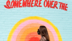 A woman wears a face mask as she walks by a mural on a street in Montreal, Monday, September 7, 2020, as the COVID-19 pandemic continues in Canada and around the world. THE CANADIAN PRESS/Graham Hughes
